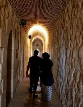 An Egyptian couple walk inside the historic Citadel of Qaitbay on the coastline in the Mediterranean city Alexandria